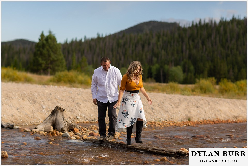 rocky mountain national park elopement wedding bride and groom walking across river on log