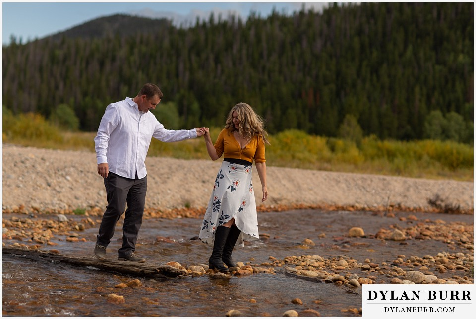 rocky mountain national park elopement wedding bride helping groom across river