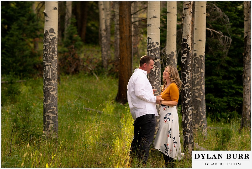 rocky mountain national park elopement wedding couple holding hands in sun and trees