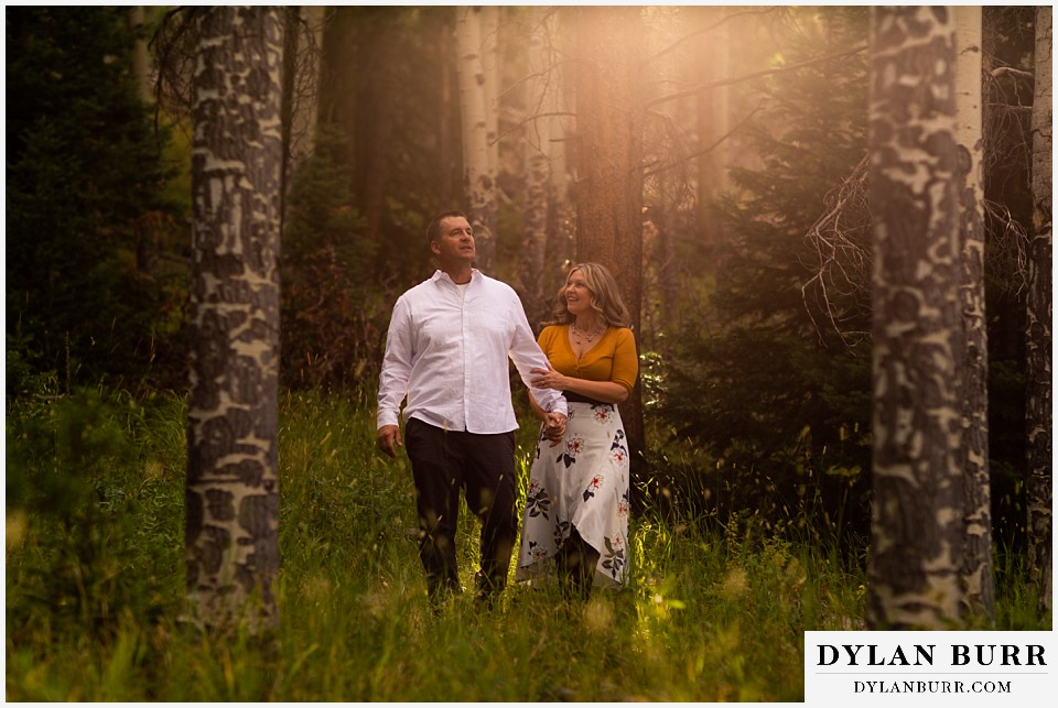 rocky mountain national park elopement wedding bride and groom walking in forest with sun glow