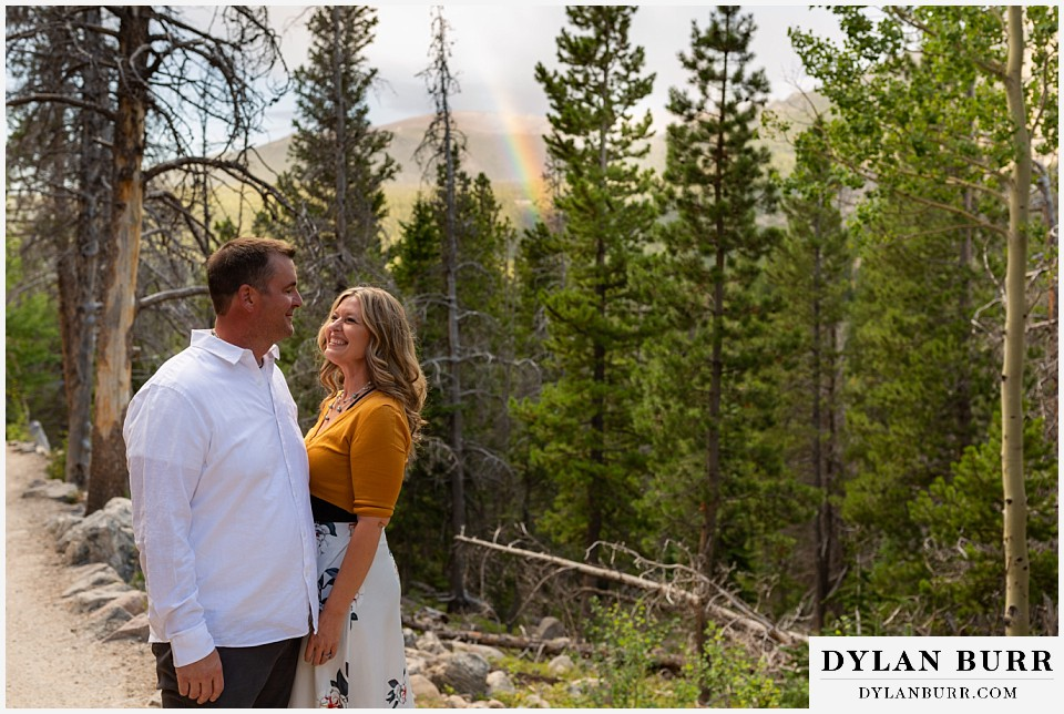 rocky mountain national park elopement wedding couple on hiking trail with rainbow in forest