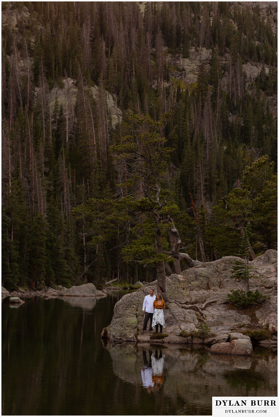 rocky mountain national park elopement wedding couple looking at their reflection in a mountain lake