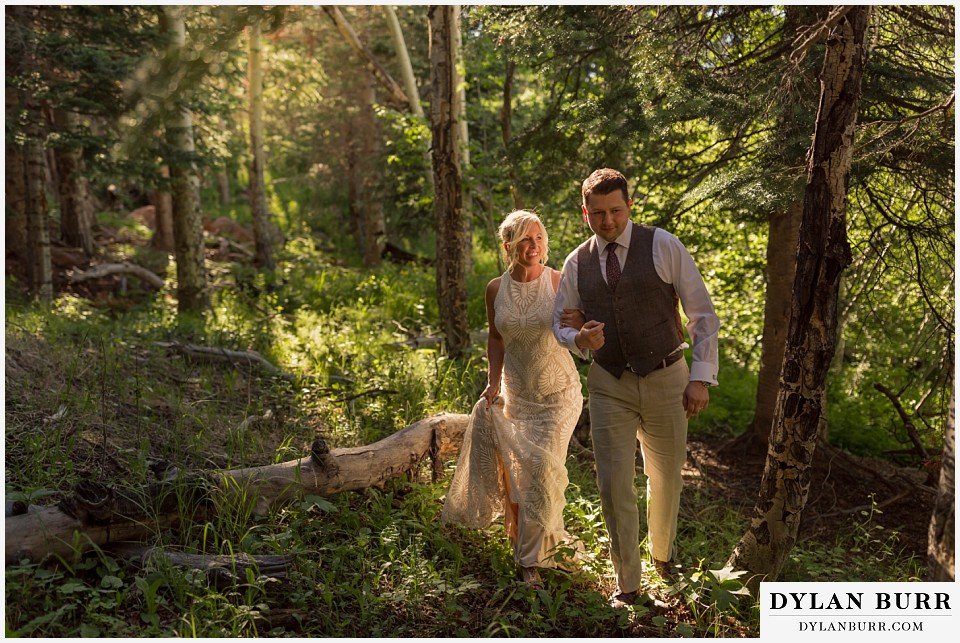 rocky mountain national park wedding elopement bride and groom walking through forest