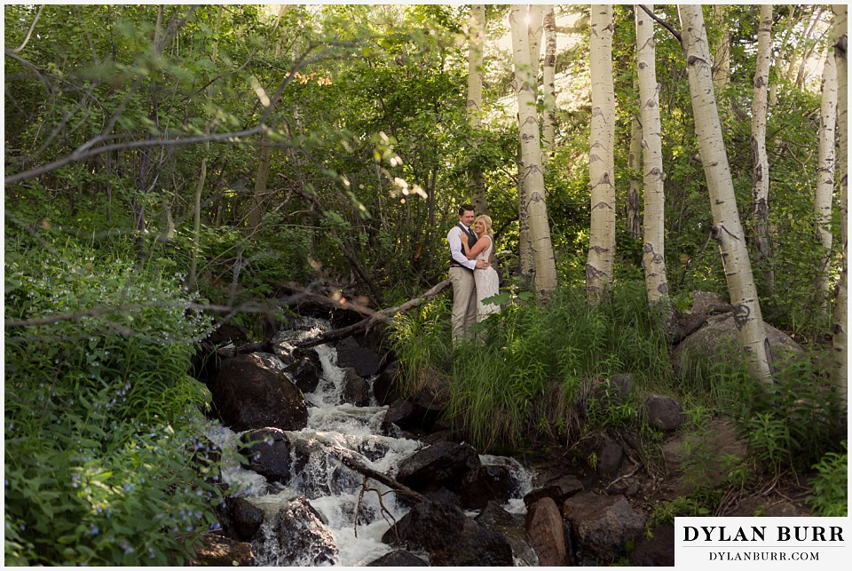 rocky mountain national park wedding elopement bride and groom near a rushing waterfall deep in forest