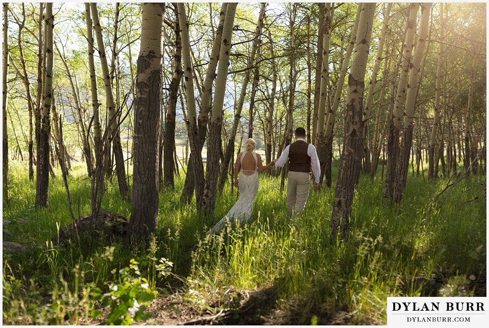 rocky mountain national park wedding elopement bride and groom walking in aspen grove
