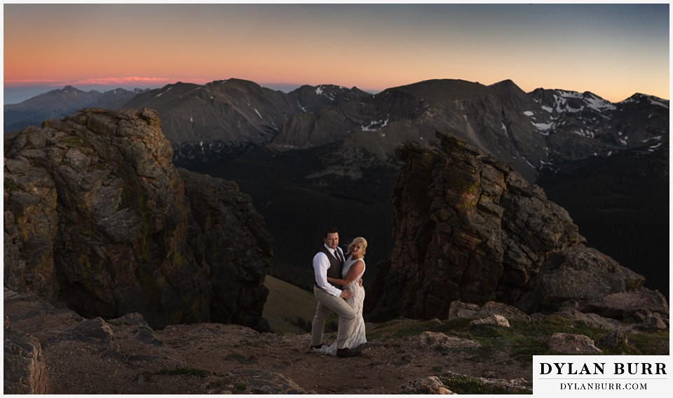 rocky mountain national park wedding elopement bride and groom look on within some mountain rocks and massive mountain range with snow behind them