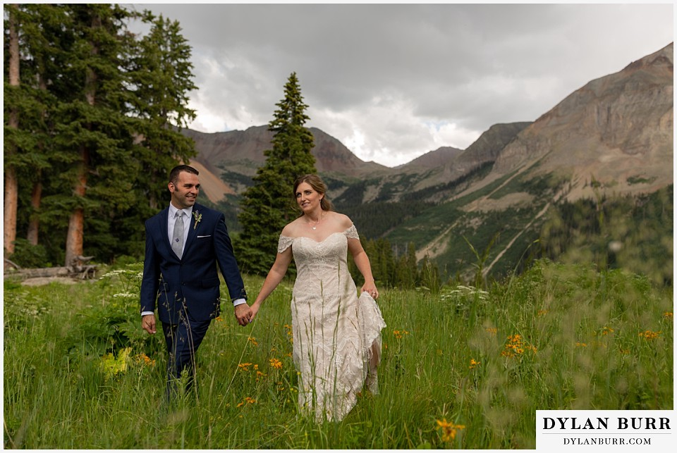 telluride colorado elopement wedding adventure bride and groom holding hands while high in mountains