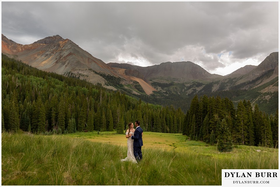 telluride colorado elopement wedding adventure bride and groom dancing in the rain in mountains