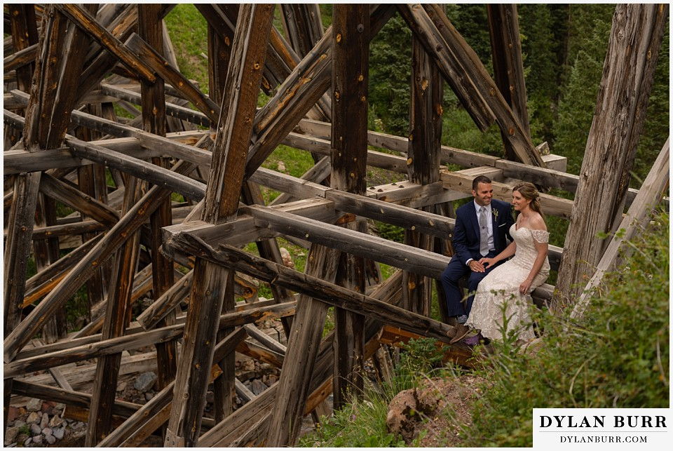 telluride colorado elopement wedding adventure bride and groom sitting on giant old wooden train bridge
