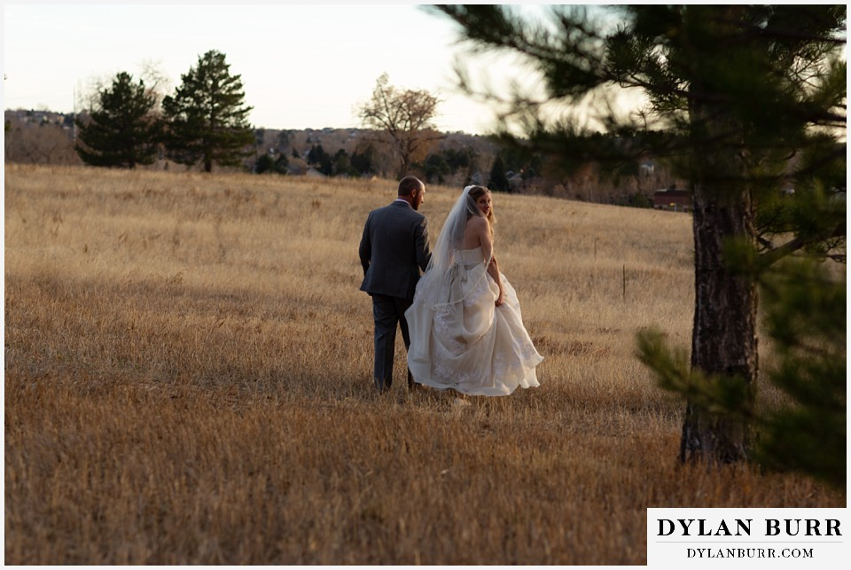 villa parker wedding parker colorado bride and groom walking out in field together