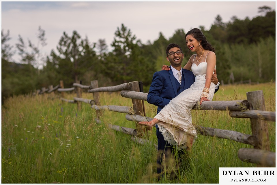 wild basin lodge hindu wedding couple sitting on fence