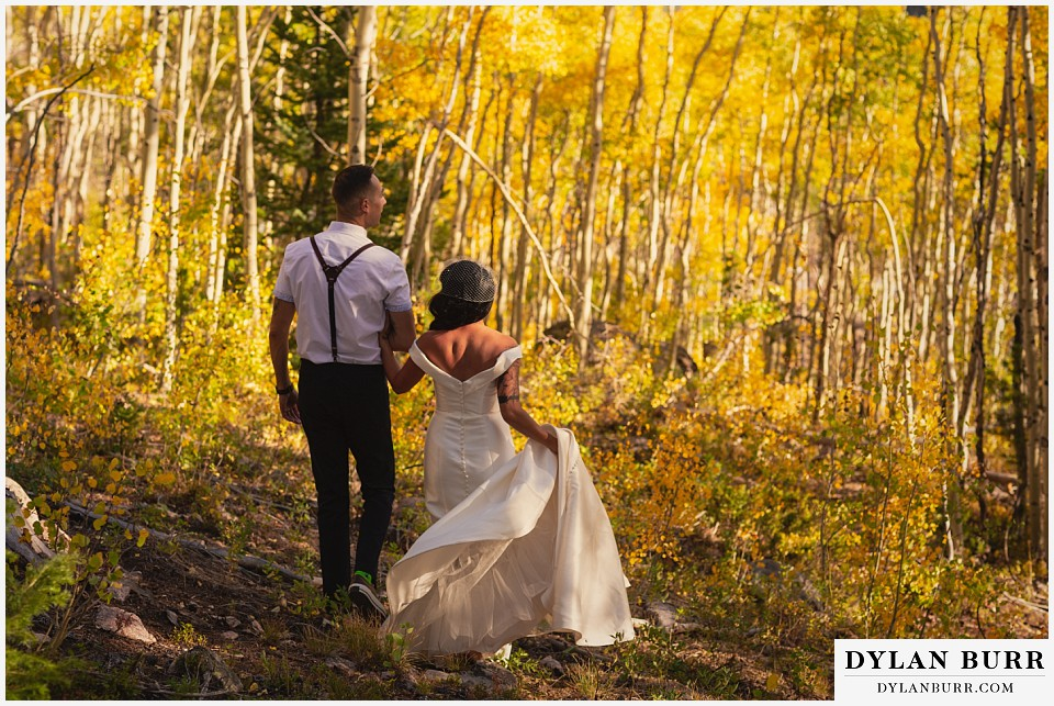 winter park mountain lodge wedding colorado bride and groom walking together in aspen trees