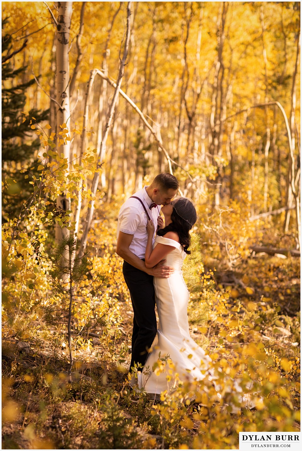 winter park mountain lodge wedding colorado bride and groom sharing a kiss surrounded by yellow aspen leaves