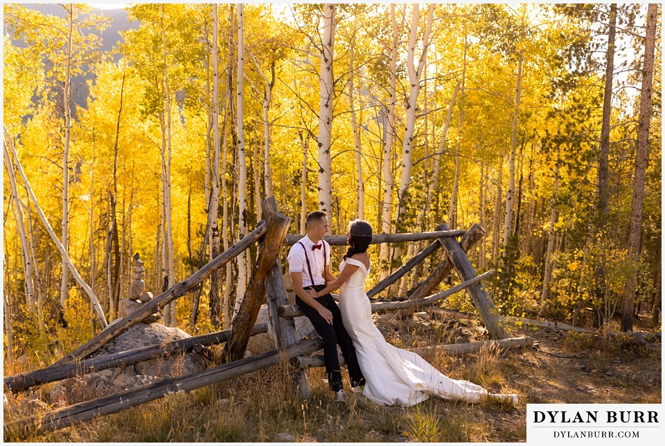 winter park mountain lodge wedding colorado bride and groom in forest near old fence