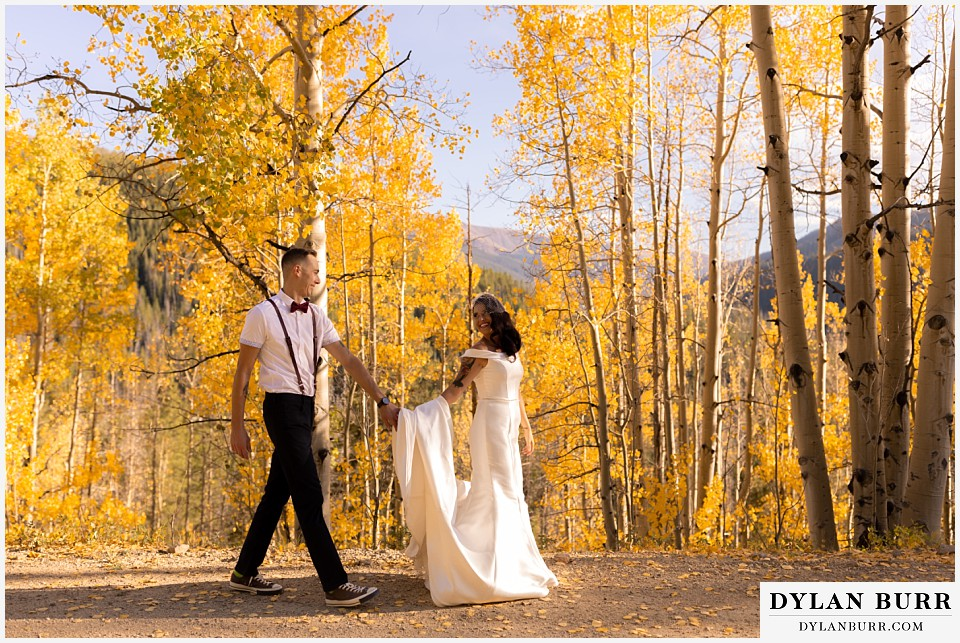 winter park mountain lodge wedding colorado bride and groom walking together on road alongside aspen trees