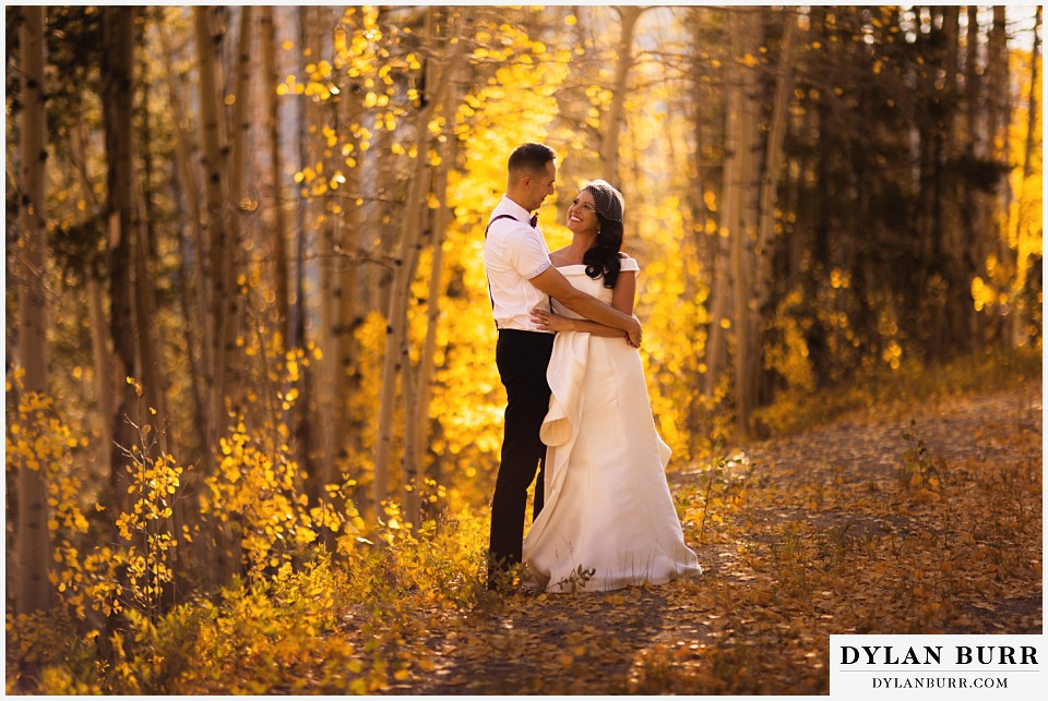 winter park mountain lodge wedding colorado bride and groom by fall leaves in forest