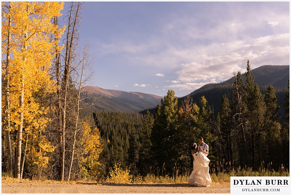winter park mountain lodge wedding colorado bride and groom dancing in forest along road