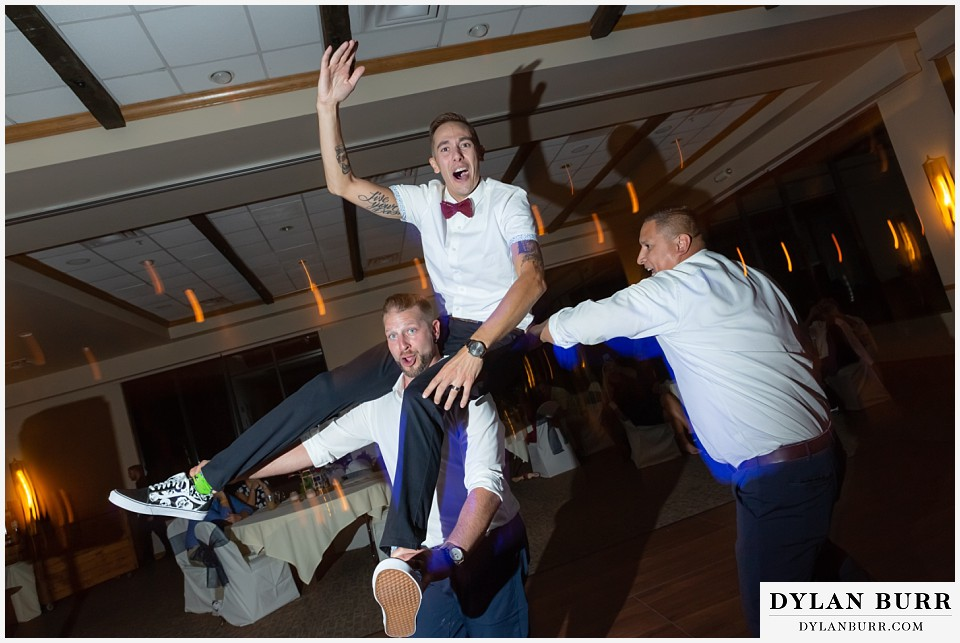 winter park mountain lodge wedding colorado groomsmen picked up groom and riding him around the dance floor